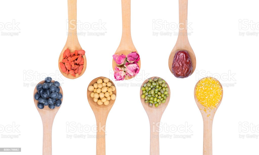 Collection of beans on wooden spoons isolated on white. Black beans, soybeans, mung bean, Chinese date, rose bud, wolfberry and corn Meal Grits. stock photo