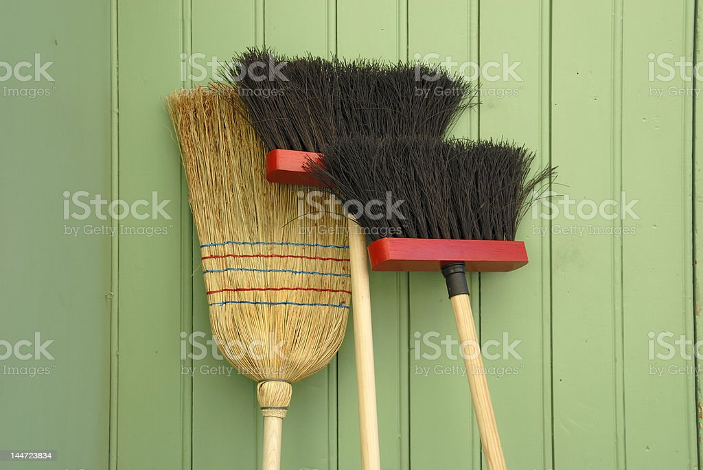 A collection of brooms against a green wall stock photo