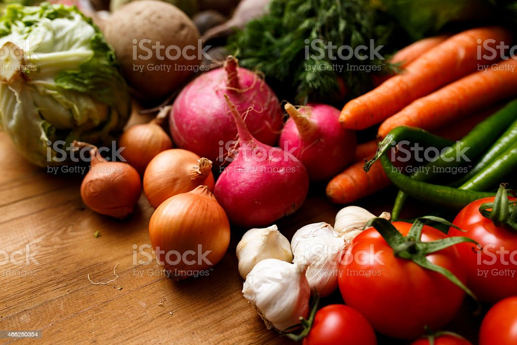 A collection of colorful fresh vegetables on a wooden table stock photo