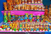 A collection of colorful traditional wooden dolls or channapatna toys are displayed for selling in handicraft fair.