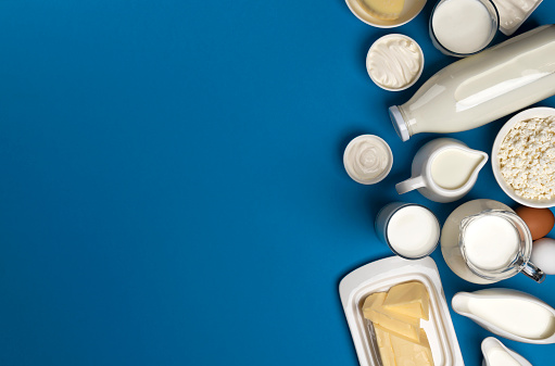 Top view of dairy products on blue background, assortment of milk, butter, sour cream and yogurt with copy space
