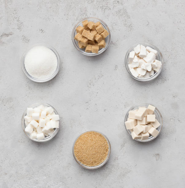 Collection of different kinds of sugar on gray background Sweet composition. Collection of sugar kinds on gray background, top view sugar cane stock pictures, royalty-free photos & images