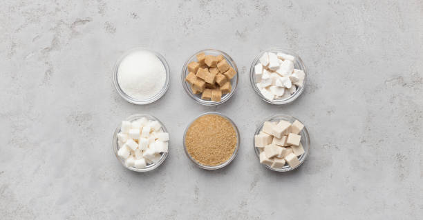 Collection of different kinds of sugar on gray background Collection of different types of brown and white sugar on gray background, panorama, top view sugar cane stock pictures, royalty-free photos & images