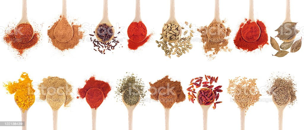 A collection of different spices on wooden spoons stock photo