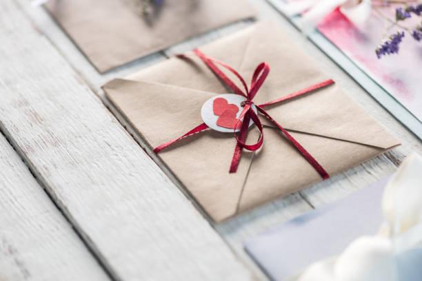 sammlung von umschlägen oder einladungen auf weißen hölzernen tischplatte, hochzeit einladung karte design-konzept - besondere geschenke stock-fotos und bilder
