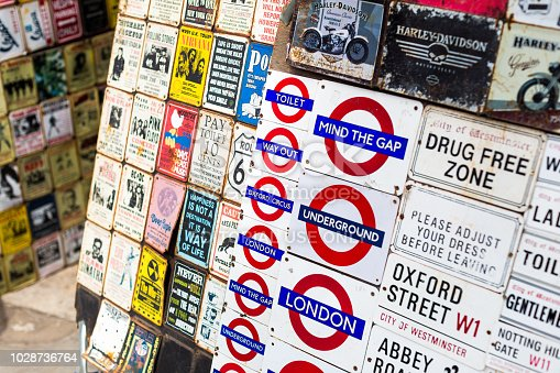 London, UK - 16 July, 2018: color image depicting a large collection of London street signs in a row at a market stall in Notting Hill, London, UK. The signs are of famous places and streets found in London, such as Piccadilly Circus, London, Eye, Downing Street and Portobello Road. There is also a collection of London Underground signs.
