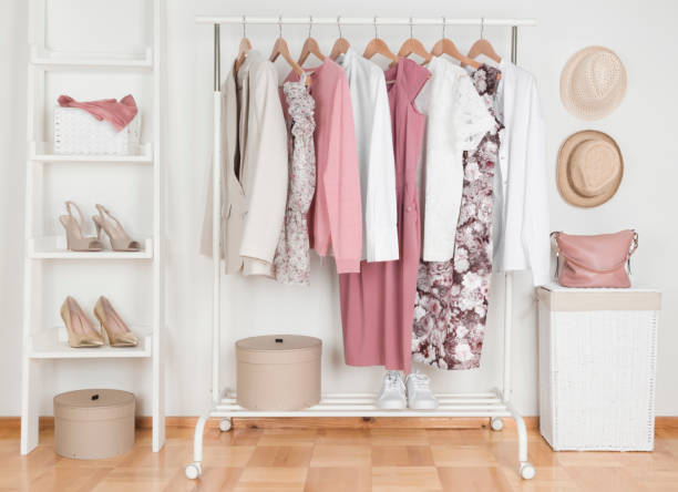 Collection of female clothes hanging on rack in dressing room stock photo