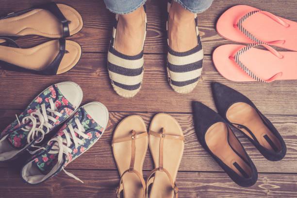 verzameling van vrouwelijke schoenen op houten vloer. - shoe stockfoto's en -beelden