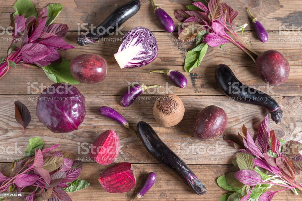 Collection of fresh purple fruit and vegetables on wooden background. stock photo