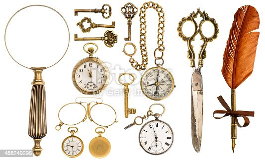 Collection of golden vintage accessories and antique objects. Old keys, clock, loupe, compass, ink feather pen, scissors, glasses isolated on white background