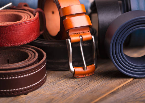 collection of leather belts on a wooden table - belt stock photos and pictures