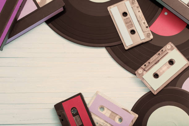 Collection of music tapes, records and video cassettes on wooden background. Retro concept stock photo