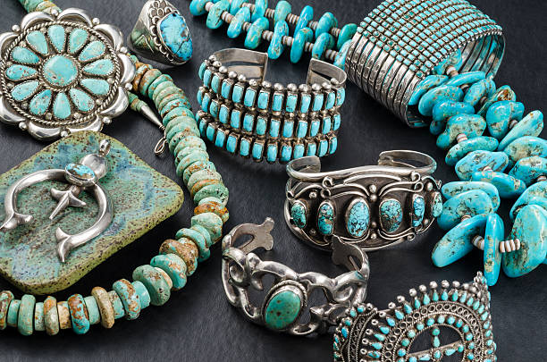 Collection of Native American Turquoise and Silver Jewelry. Vintage Native American Turquoise and Sterling Silver Jewelry, Necklaces, Bracelets and Concho on a black background. turquoise colored stock pictures, royalty-free photos & images