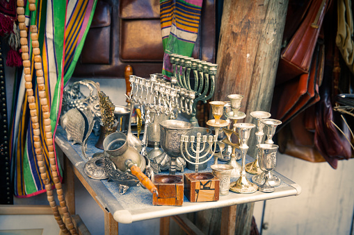 Table with menorah and Kiddush wine cups,and other items at  the flea market. - Tel Aviv, Israel