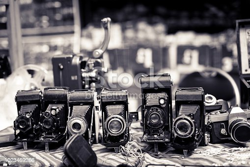 Close up toned monochrome image depicting a display of retro vintage cameras in a row and for sale at an outdoors street market in Notting Hill, London, UK. Focus is on the cameras while the street is defocused in the background. Room for copy space.