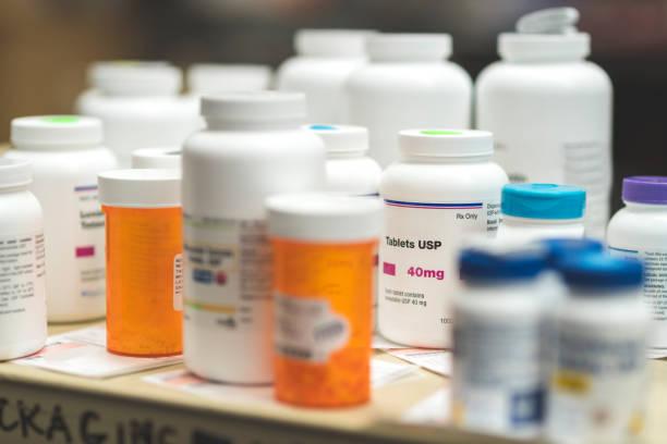 collection of pill bottles in pharmacy - капсула стоковые фото и изображения