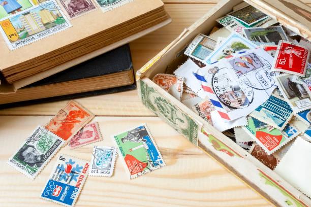 Collection de timbres-poste de différents pays dans l'ancienne boîte et le support de timbre couché sur une table en bois - Photo
