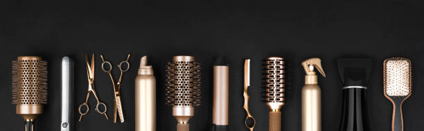 Collection of professional hair dresser tools arranged on dark background stock photo