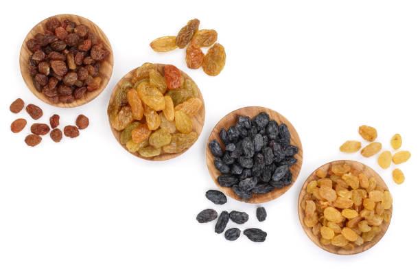 Collection de raisins secs dans un bol en bois isolé sur fond blanc avec espace de copie pour votre texte. Vue de dessus. Poser de plat - Photo