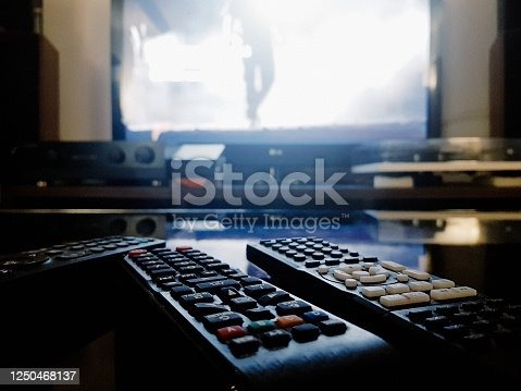 Remote controls resting on a coffee table with a TV program in the background.