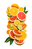 Collection of sliced citrus fruits shot from above on white background. The composition includes slices of grapefruit, orange, lemon, lime, tangerine and kumquat. Some citrus tree leaves complete the composition. High resolution 42Mp studio digital capture taken with Sony A7rii and Sony FE 90mm f2.8 macro G OSS lens