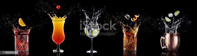 fruit falling into a collection of splashing cocktails isolated on black background