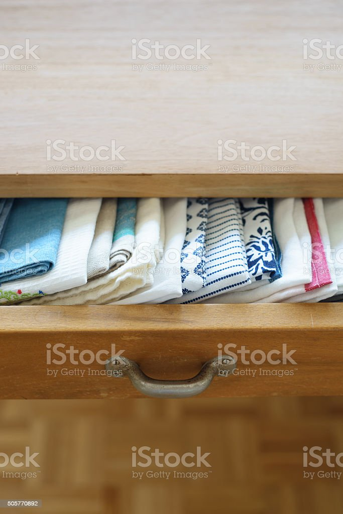 Collection of tea towels in a drawer in a raw stock photo