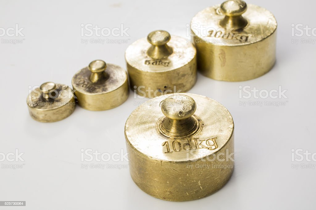 Collection of Thee Vintage Golden And Silver Calibration Weights stock photo