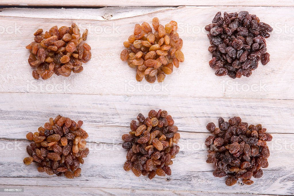 Collection of various raisins isolated on white wood background stock photo