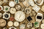 Retro styled image of a collection of vintage rusty watches and parts