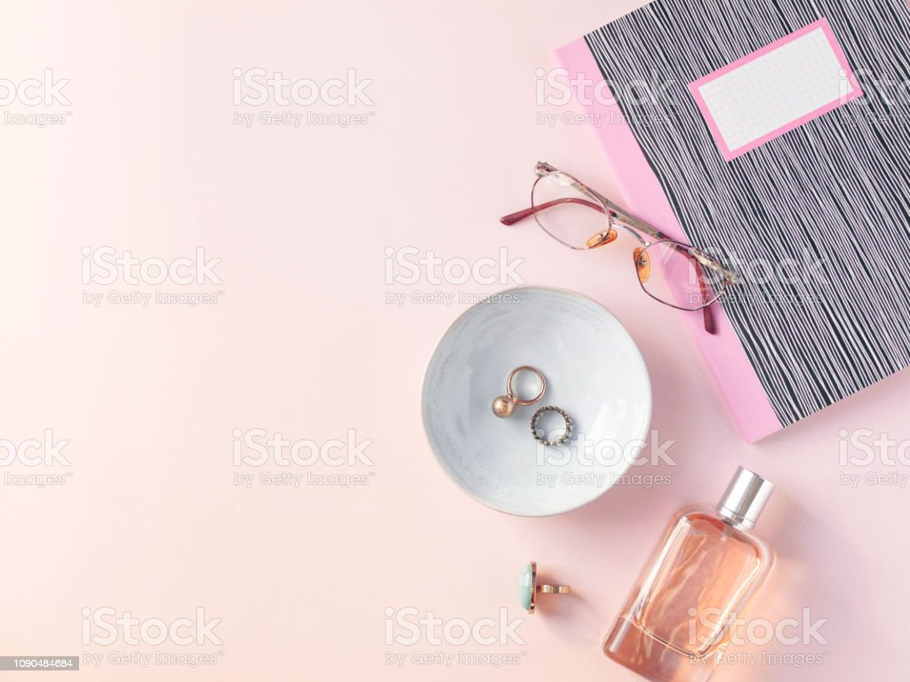Collection of woman's accessories like jewelry, perfume, glasses, notebook isolated on pastel pink background. Flat lay. Top view. Copy space