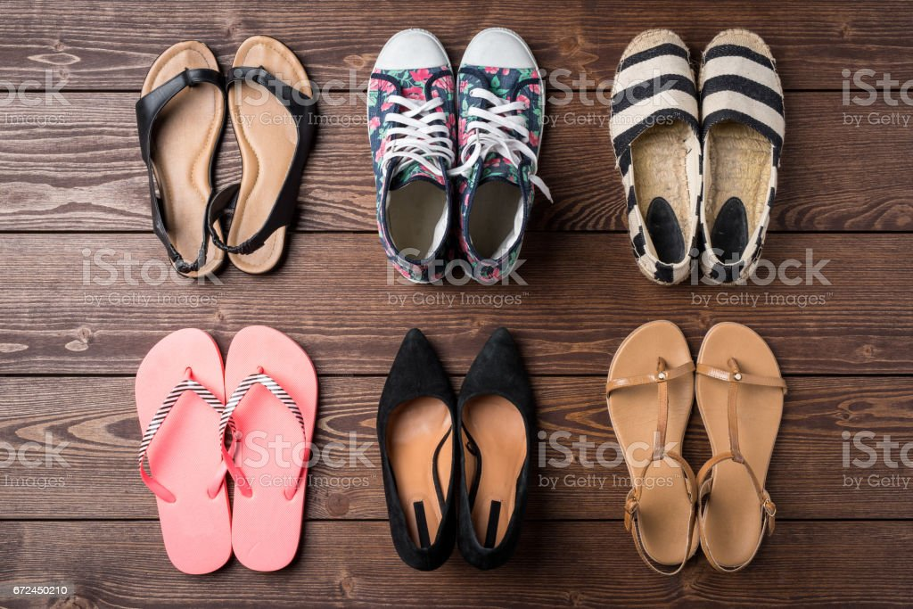 Collection of women's shoes on wooden background stock photo