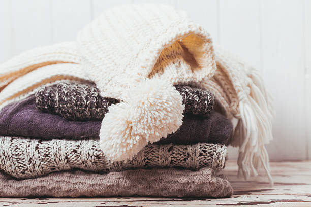 Collection of woolen clothes Stack warm knitted sweaters, scarf and hat in white and gray shades warm clothing stock pictures, royalty-free photos & images
