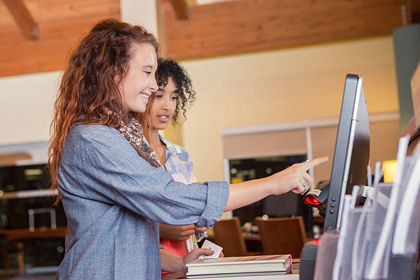 college age customers using self check out in public library - interactivity stock photos and pictures