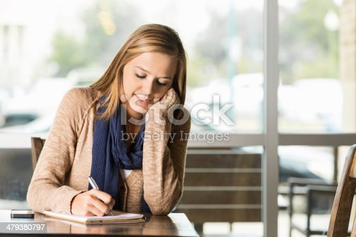 1183295518 istock photo College age girl writing in journal at coffee shop 479380797
