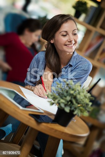 694187664 istock photo College age girl writing in journal at coffee shop 621909470