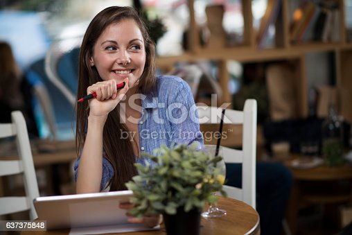 694187664 istock photo College age girl writing in journal at coffee shop 637375848