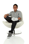 istock College age man relaxing in a modern chair 471894315