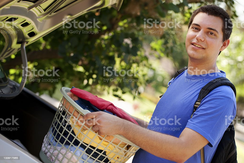 College boy lifting basket of laundry stock photo