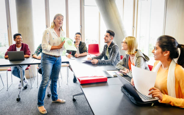 College classroom with mature female teacher and young multi ethnic students stock photo