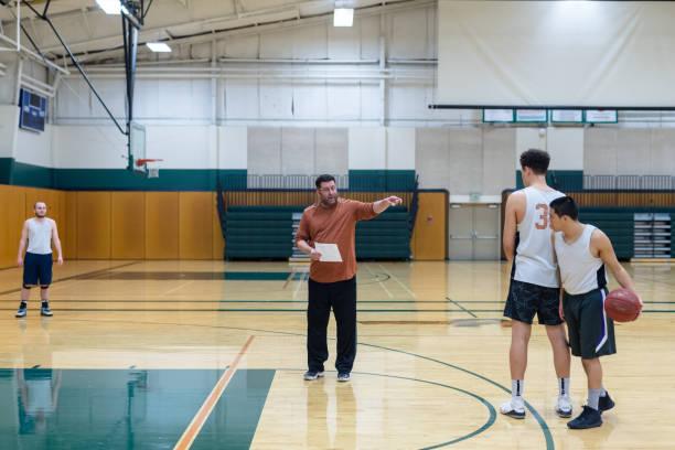 College coach running men's basketball practice stock photo