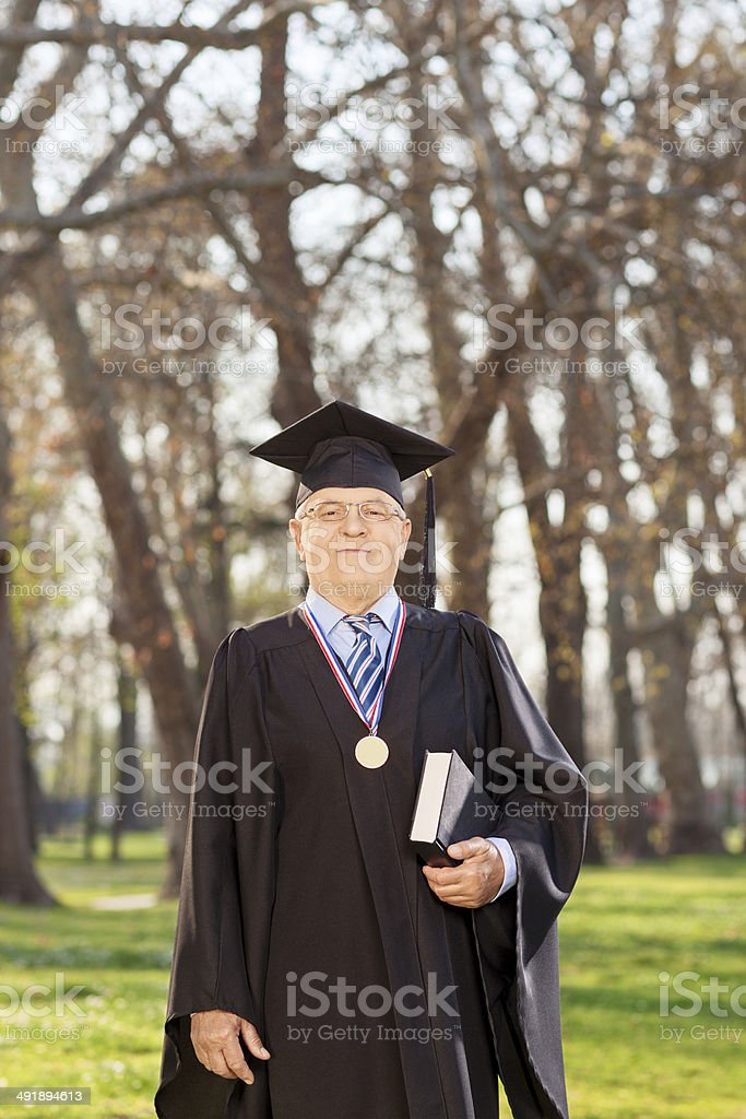 College dean holding a book outdoors stock photo