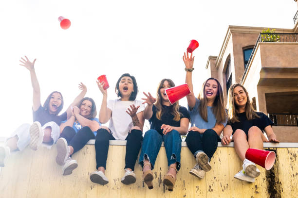 College Female Roommates Throwing Red Cups Off The Roof Six college roommates sit in a row on top of the garage. They throw their cups off the roof at the camera down below. Shot from a low angle. peer pressure stock pictures, royalty-free photos & images