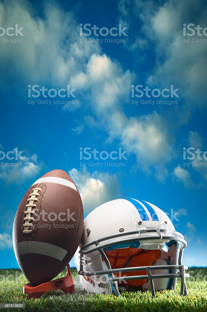 This is a photo of an American football leaning against a white...
