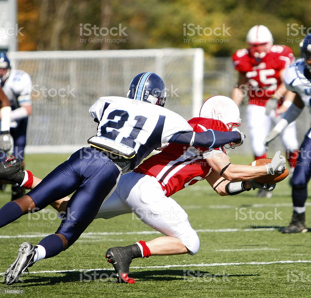 College Football - Catch and Tackle The running back dives for the first down with the defender on his back. Activity Stock Photo