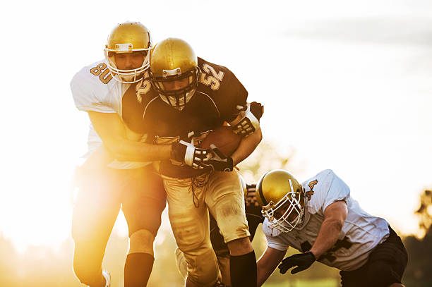 College Football - Catch and Tackle. American football players in action on the playing field. wide receiver athlete stock pictures, royalty-free photos & images