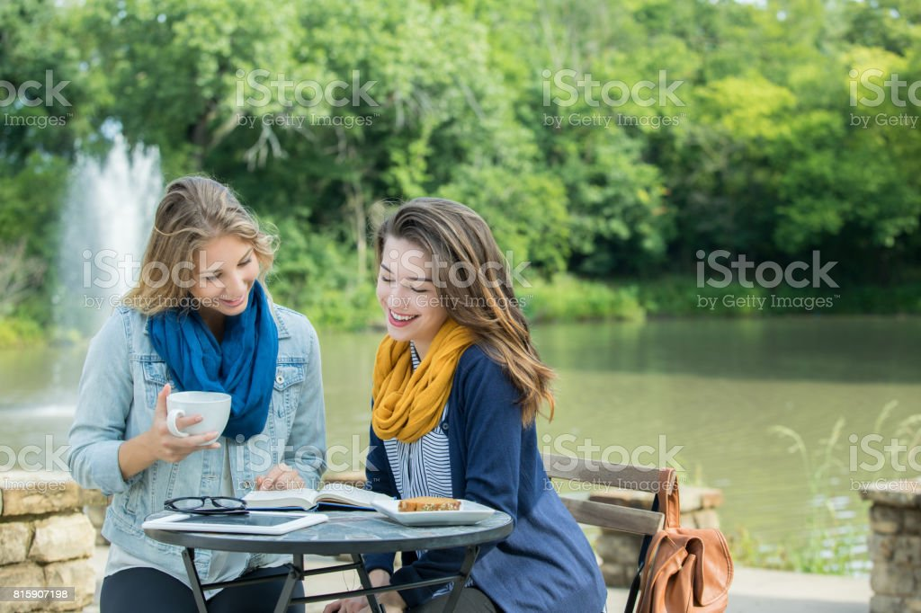 College friends study together at outdoor cafe stock photo