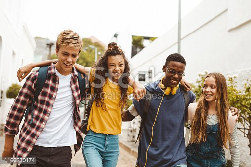 Smiling teenage friends wearing college bags having fun walking together in the street. Happy teenage boys and girls walking in an alley holding each other.