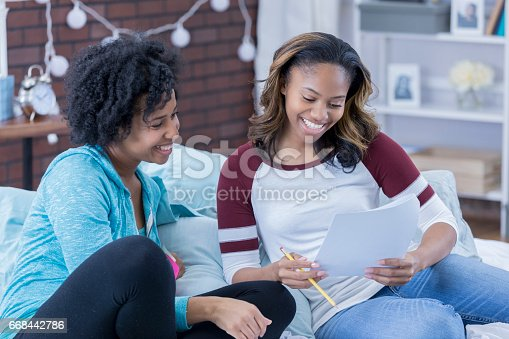 istock College friends work together on an assignment 668442786