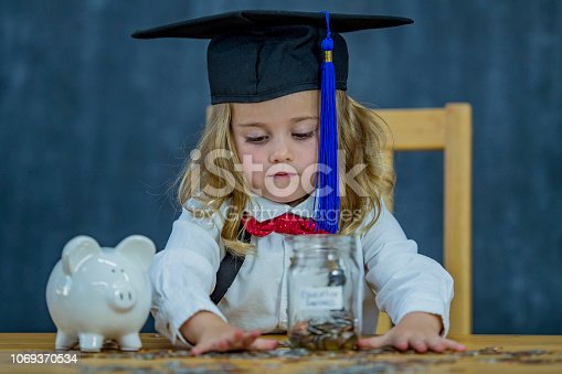 A toddler girl in a graduation cap is sitting at a table counting a pile of change. There is a piggy bank on the table.